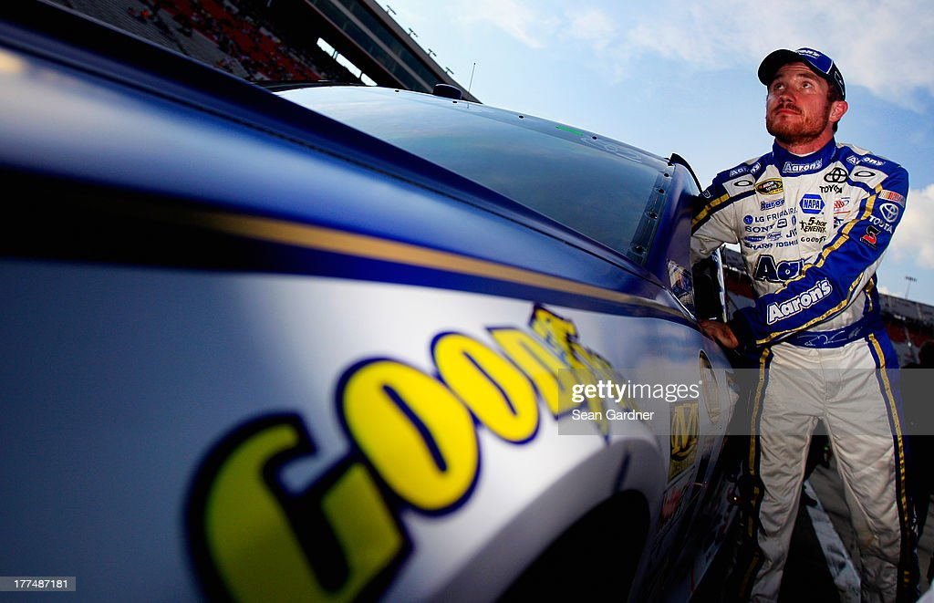 Brian Vickers, driver of the #55 Aaron's Dream Machine Toyota, climbs from his car after qualifying for the NASCAR Sprint Cup Series IRWIN Tools Night Race at Bristol Motor Speedway on August 23, 2013 in Bristol, Tennessee.