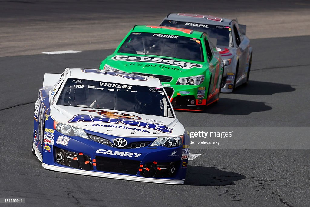Brian Vickers, driver of the #55 Aaron's Dream Machine Toyota, leads Danica Patrick, driver of the #10 GoDaddy Chevrolet, and Travis Kvapil, driver of the #93 Burger King / Dr. Pepper Toyota, during the NASCAR Sprint Cup Series Sylvania 300 at New Hampshire Motor Speedway on September 22, 2013 in Loudon, New Hampshire.