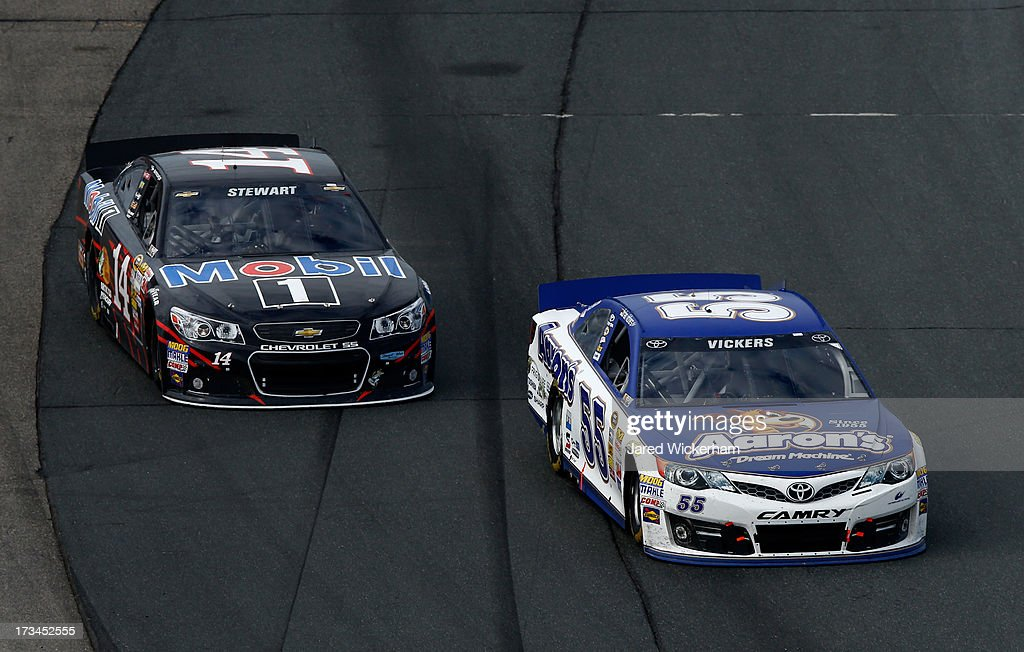 Brian Vickers, driver of the #55 Aaron's Dream Machine Toyota, passes Tony Stewart, driver of the #14 Mobil 1 Chevrolet, in the final laps of the NASCAR Sprint Cup Series Camping World RV Sales 301 at New Hampshire Motor Speedway on July 14, 2013 in Loudon, New Hampshire.