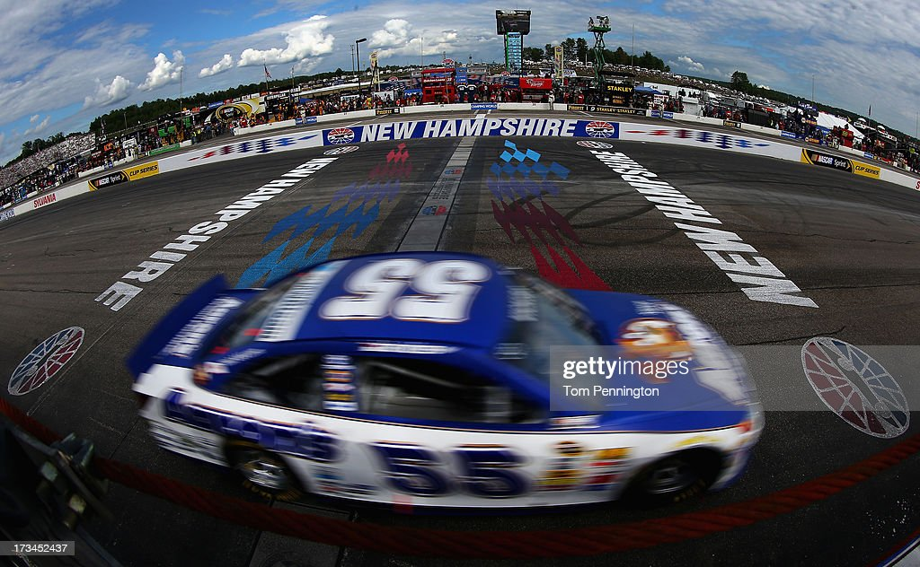 Brian Vickers, driver of the #55 Aaron's Dream Machine Toyota, takes the checkered flag as he crosses the finish line to win the NASCAR Sprint Cup Series Camping World RV Sales 301 at New Hampshire Motor Speedway on July 14, 2013 in Loudon, New Hampshire.