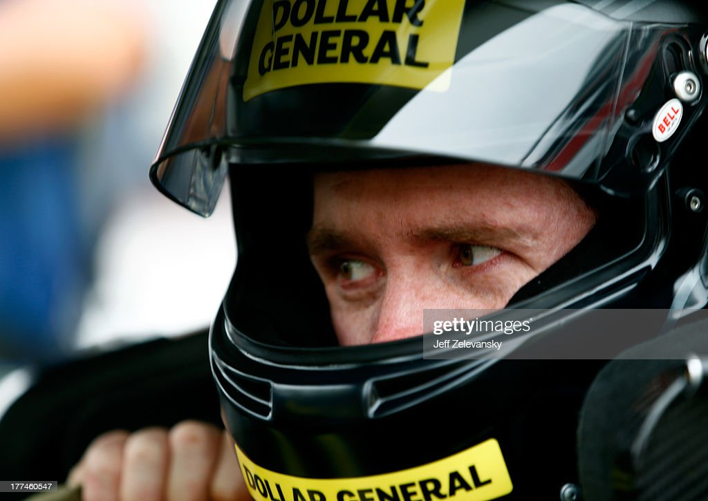 Brian Vickers, driver of the #20 Dollar General Toyota, adjusts his helmet in his car during practice for the NASCAR Nationwide Series Food City 250 at Bristol Motor Speedway on August 23, 2013 in Bristol, Tennessee.
