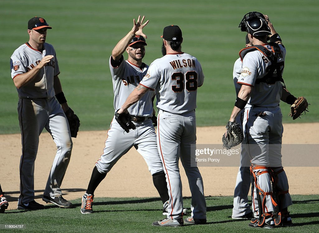 Brian Wilson #38 of the San Francisco Giants, left, is congratulated by teammates after the final out during the 11th inning of a baseball game against the San Diego Padres at Petco Park on July 17, 2011 in San Diego, California.