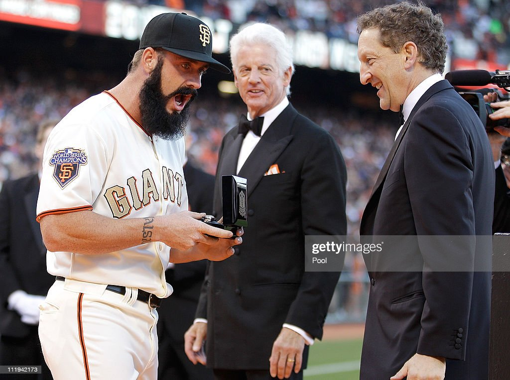 Brian Wilson #38 of the San Francisco Giants reacts as he receives his World Series ring from Giants owner Bill Neukom (C) and Giants president Larry Baer before the start of the game against the St. Louis Cardinals at AT&T Park on April 9, 2011 in San Francisco, California.