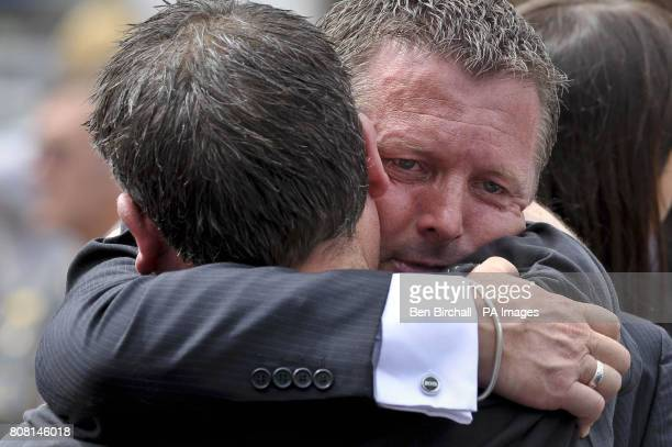 Brian Wright the half brother of Major Josh Bowman is hugged from a friend after the funeral cortege containing his half brother and three fellow...