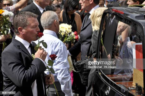 Brian Wright the half brother of Major Josh Bowman of 1st Battalion The Royal Gurkha Rifles kisses a single rose before placing it on the hearse...