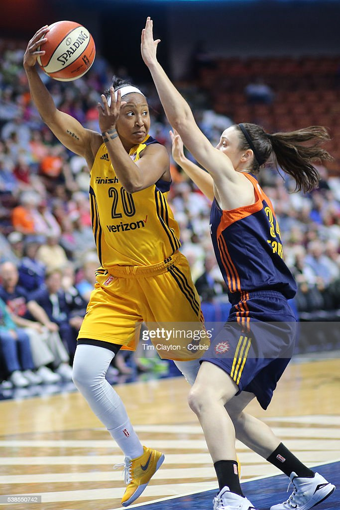 Briann January of the Indiana Fever passes over Kelly Faris of the Connecticut Sun during the Indiana Fever Vs Connecticut Sun WNBA regular season...