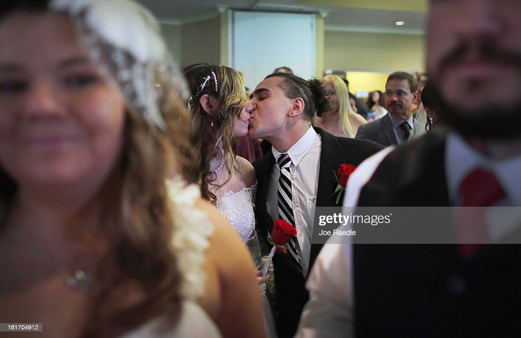 Brianna Astudillo and Matias Astudillo (L-R) kiss after being wed during a group Valentine's day wedding at the National Croquet Center on February 14, 2013 in West Palm Beach, Florida. The group wedding ceremony is put on by the Palm Beach Country Clerk & Comptroller's office and approximately 40 couples to tied the knot.