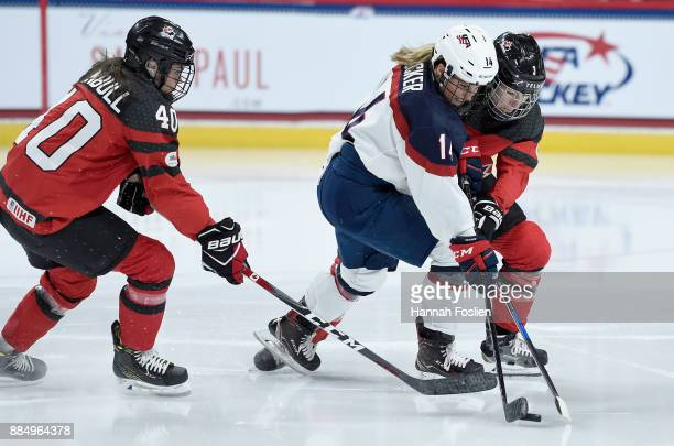 Brianna Decker of the United States controls the puck against Blayre Turnbull and Jocelyne Larocque of Canada during the second period of the game on...