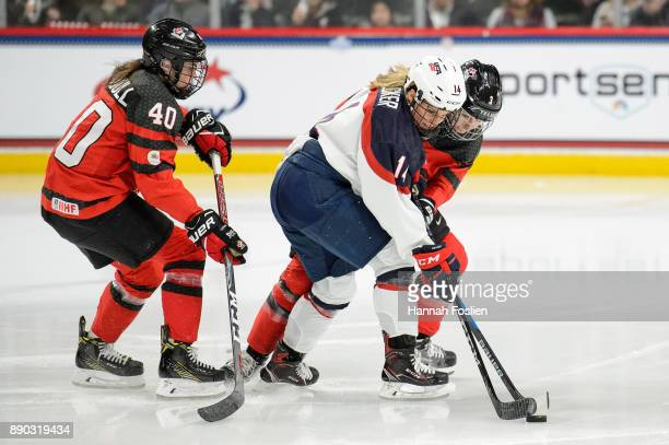 Brianna Decker of the United States controls the puck against Blayre Turnbull and Jocelyne Larocque of Canada during the game on December 3 2017 at...