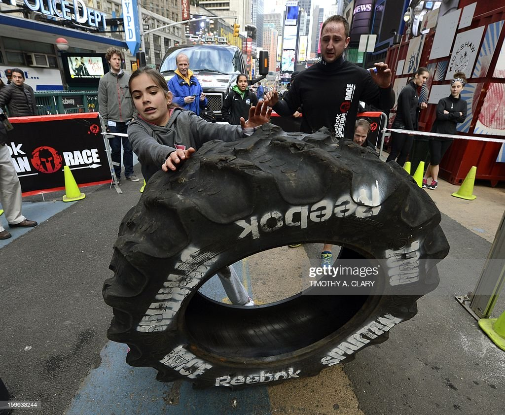 Brianna Lennon (C-L) tries an obstacle course on January 17, 2013, during a demonstration for the 'Spartan Race' scheduled for April 2013. The 'Spartan Race Times Square Challenge' demonstration and news conference was held at Times Square in New York to launch the multi-year business partnership between Reebok and Spartan Race. AFP PHOTO / TIMOTHY A. CLARY