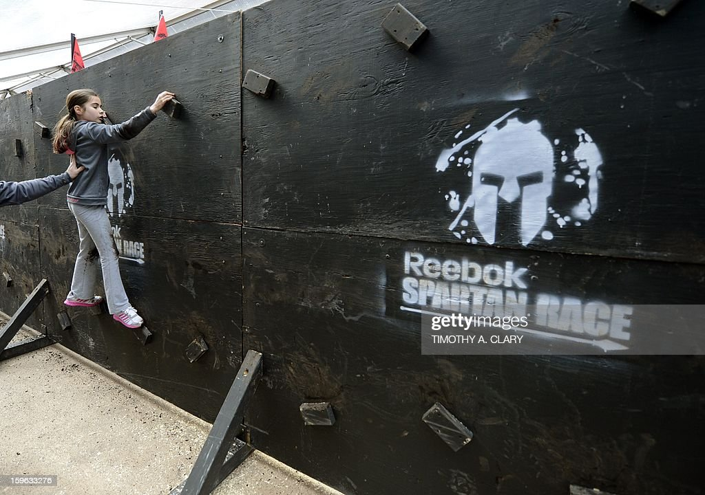 Brianna Lennon tries an obstacle course on January 17, 2013, during a demonstration for the 'Spartan Race' scheduled for April 2013. The 'Spartan Race Times Square Challenge' demonstration and news conference was held at Times Square in New York to launch the multi-year business partnership between Reebok and Spartan Race.