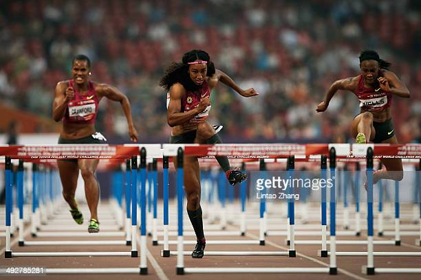 Brianna Rollins of the United States races as her teammate Kellie Wells and Virginia Crawford during 2014 IAAF Beijing Challenge at National Sports...