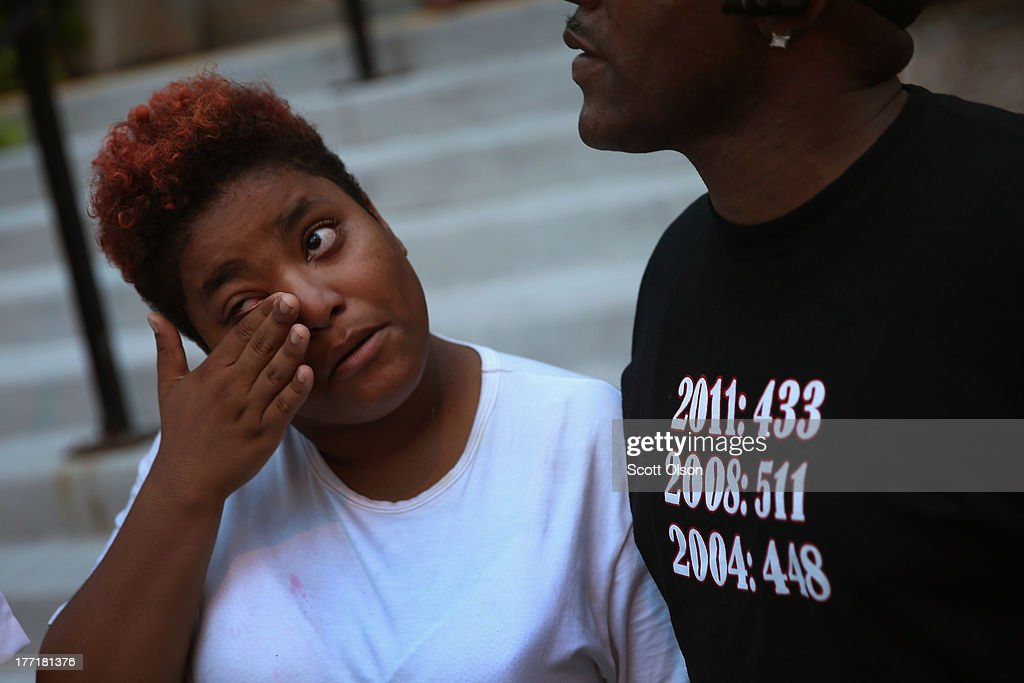 Brianna Williams wipes away tears as she tells Willie Williams Jr.about her boyfriend Darius Oliver following a prayer vigil outside the Uptown Baptist Church August 21, 2013 in Chicago, Illinois. Oliver, one of five people who were shot while standing in front of the church on August 19, remains on life support. On Willie Williams Jr.'s shirt are annual murder tallies for the city of Chicago. Williams Jr.'s son was murdered in 2006. He was 17-years-old.