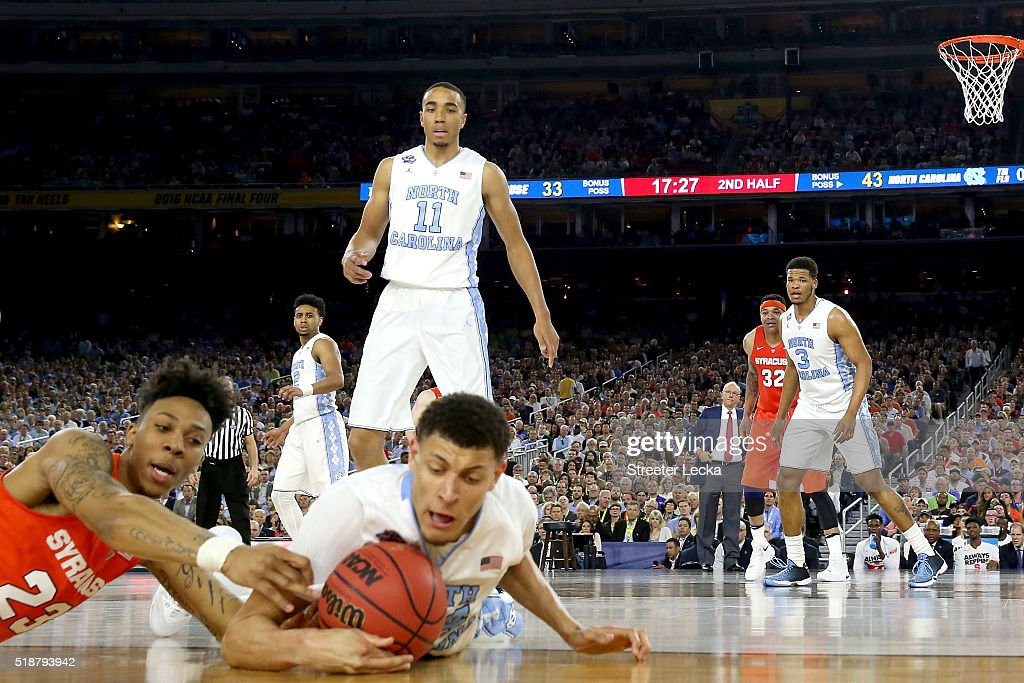Brice Johnson of the North Carolina Tar Heels looks on as Justin Jackson dives for a loose ball against Malachi Richardson of the Syracuse Orange in...