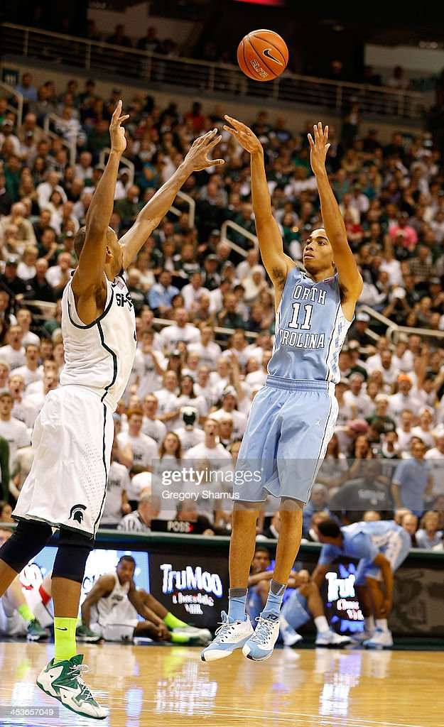 Brice Johnson #11 of the North Carolina Tar Heels takes a first half shot over <a gi-track='captionPersonalityLinkClicked' href=/galleries/search?phrase=Adreian+Payne&family=editorial&specificpeople=7367769 ng-click='$event.stopPropagation()'>Adreian Payne</a> #5 of the Michigan State Spartans at the Jack T. Breslin Student Events Center on December 4, 2013 in East Lansing, Michigan. North Carolina won the game 79-65.