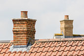 Brick chimney stack on modern contemporary house roof top. Urban housing estate tiled roof in close-up.