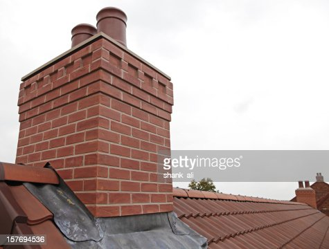 Brick chimney with two chutes sitting atop shingled roof