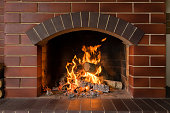 Firewood and hot coals burn in a brick fireplace with bright fire
