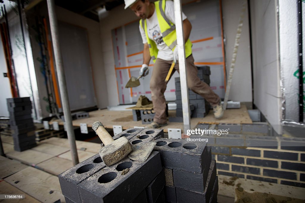 A brick layer holds a trowel as he works at the Oval Quarter, a shared ownership, private and social residential housing complex developed by Higgins Group Plc in partnership with Nottinghill Housing and Pinnacle Regeneration Group, in London, U.K., on Monday, Aug. 5, 2013. U.K. house prices rose 0.8 percent in July, from 0.3 percent the previous month, Nationwide Building Society said. Photographer: Simon Dawson/Bloomberg via Getty Images