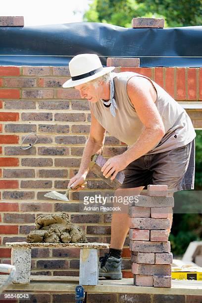 Brick mason repairing wall