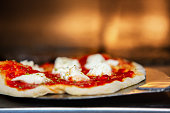 Small handmade pizza with cheese, pizza sauce and crust loading into an old fashioned rustic brick pizza oven with flames