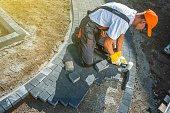 Brick Paving Works. Professional Caucasian Worker Building Block Paved Hardstanding Garden Path