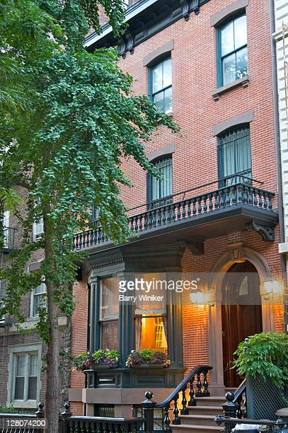 Brick townhouse with balcony and balustrade, stoop and grillwork, at dusk, Brooklyn Heights, Brooklyn, New York