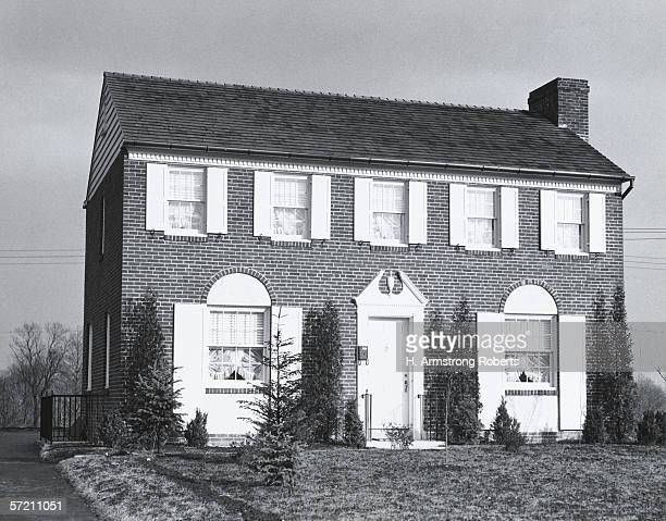 Brick two storey suburban house with shuttered windows and juniper shrubs in front yard