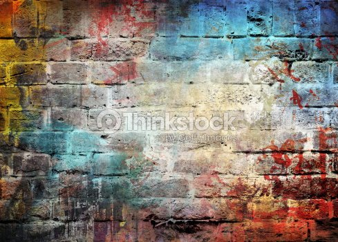 Brick wall with letters and different colors splattered on : Stock Photo