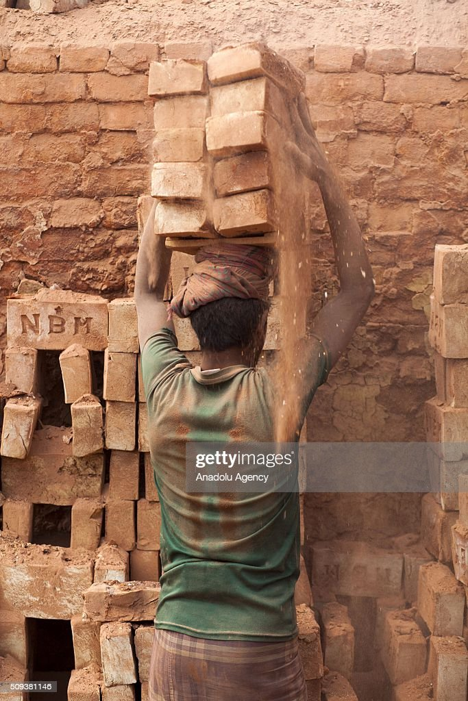 Brick worker balancing huge stacks of the blocks on his head as he carries them from the kiln near Dhaka, Bangladesh on February 10, 2016. About 11,000 brickfields are established across Bangladesh to meet the growing demand of construction works as urbanization rises rapidly in the country.
