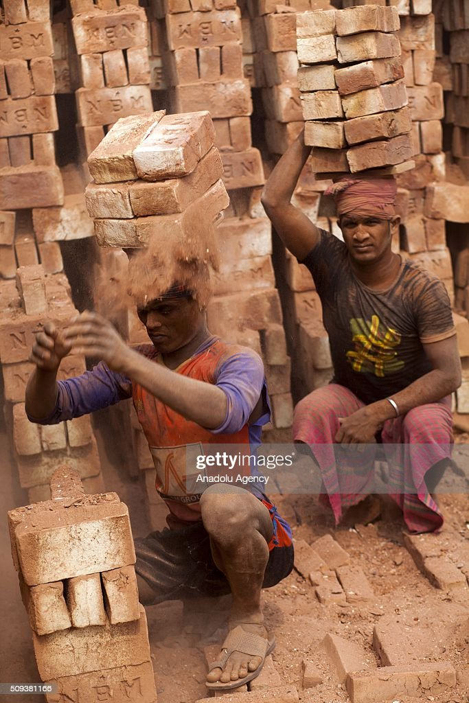 Brick workers balancing huge stacks of the blocks on their heads as the carry them from the kiln near Dhaka, Bangladesh on February 10, 2016. About 11,000 brickfields are established across Bangladesh to meet the growing demand of construction works as urbanization rises rapidly in the country.
