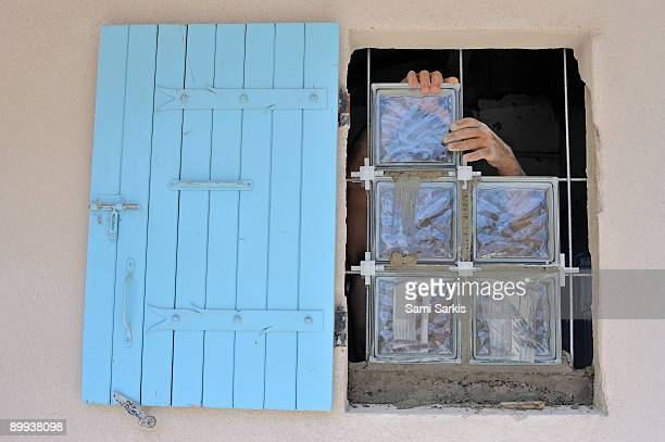 Bricklayer adjusting glass cubes windows
