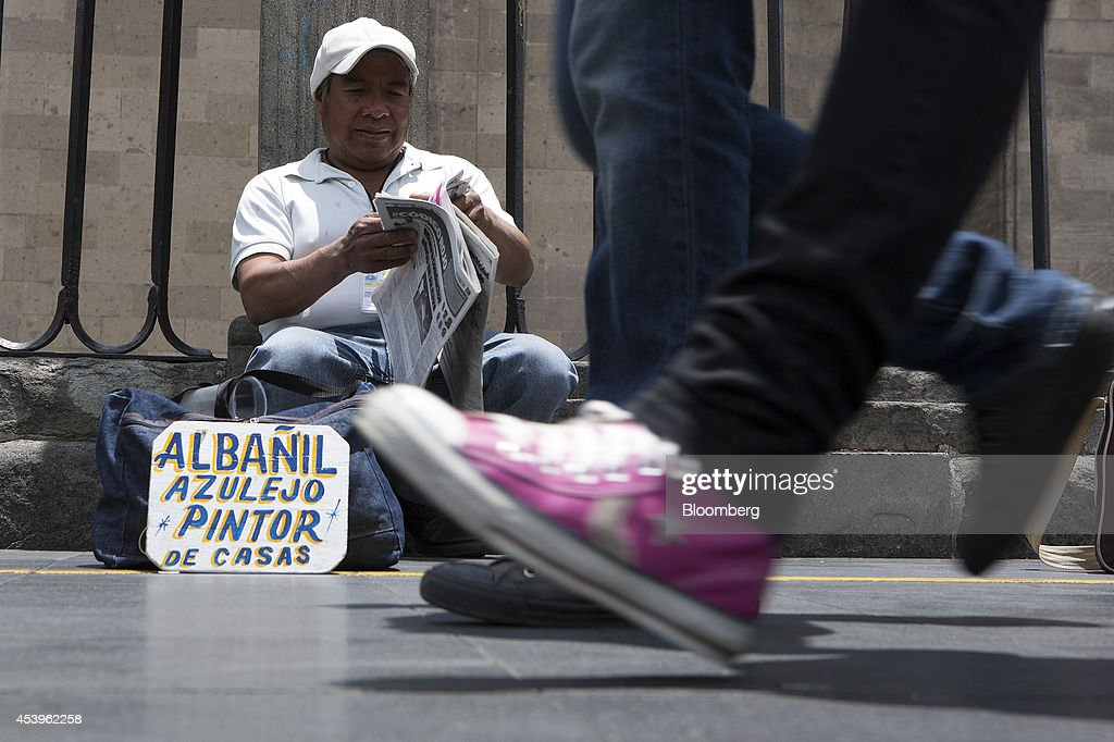 A bricklayer and painter looking for work sits behind a sign advertising his services in the traditional main plaza known as the Zocalo in Mexico City, Mexico, on Thursday, Aug. 21, 2014. Mexican consumer prices rose more than analysts expected in the first half of August and the unemployment rate rose to 5.47 percent in July compared with 4.8 percent in June. Photographer: Susana Gonzalez/Bloomberg via Getty Images