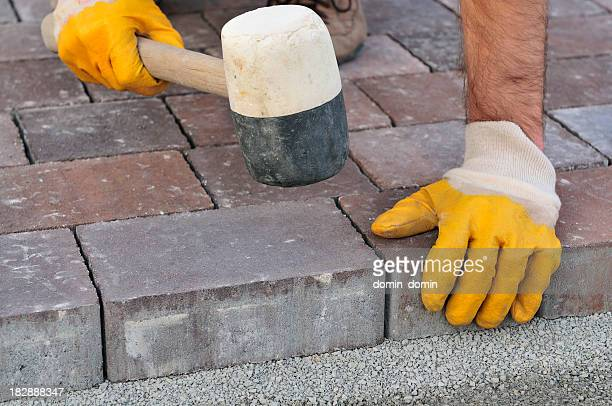Bricklayer arranges cobblestones, close-up, hands in protective gloves, rubber mallet