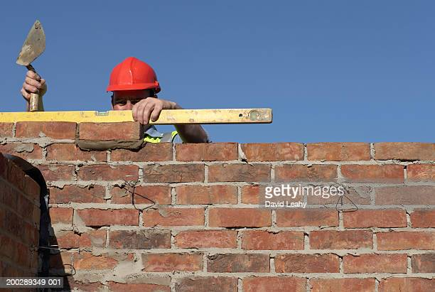 Bricklayer checking wall with spirit level
