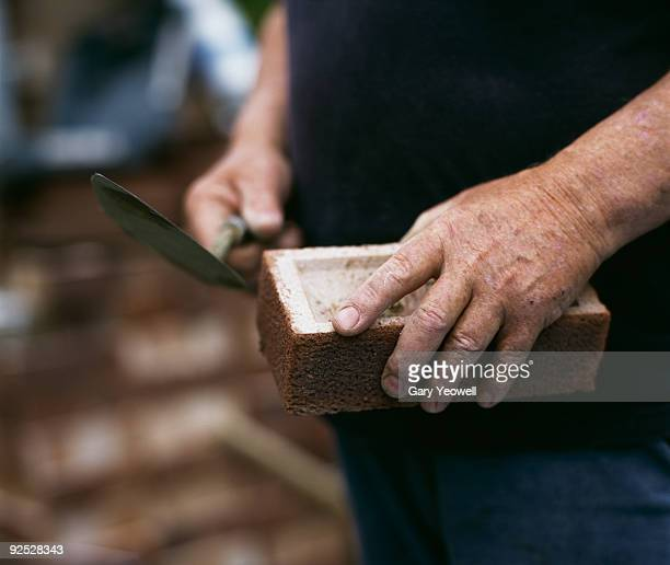 Bricklayer holding a brick and trowel