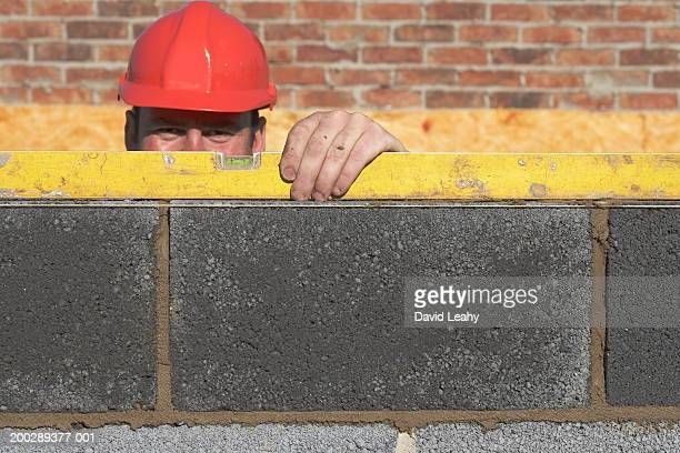 Bricklayer measuring wall with spirit level