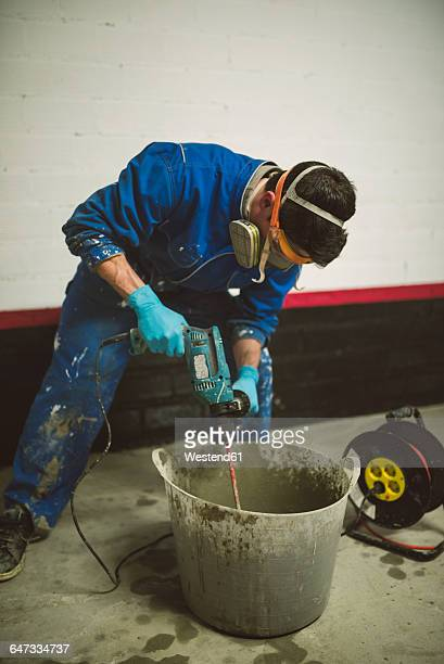 Bricklayer mixing cement in bucket