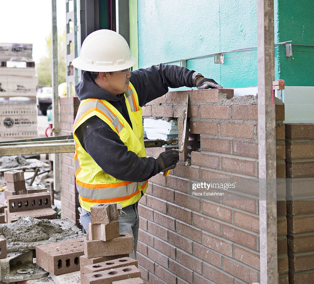 Bricklayer on new construction site : Stock Photo
