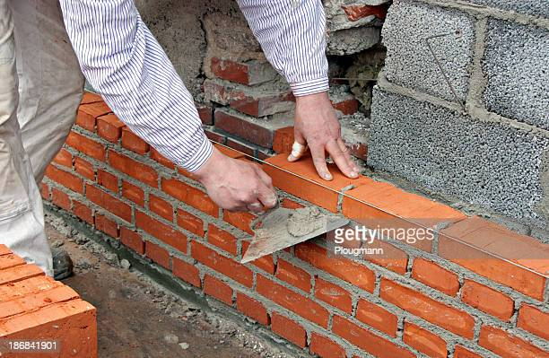 Bricklayer raising a wall