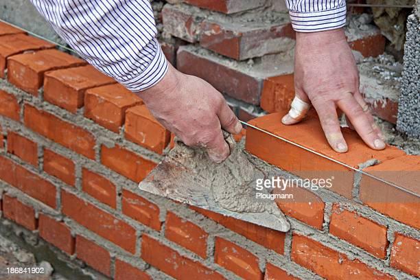 Maçon pose un mur