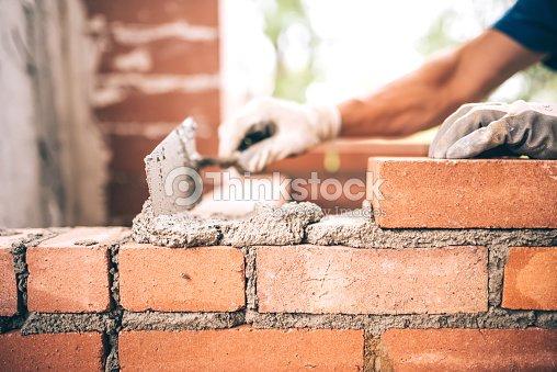 Bricklayer worker installing brick masonry on exterior wall : Stock Photo
