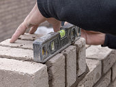 A bricklayer with his fingers outstretched, examining the level of the wall he is building, with the aid of a spirit level laid horizontally across the bricks he has built up, while still able to move