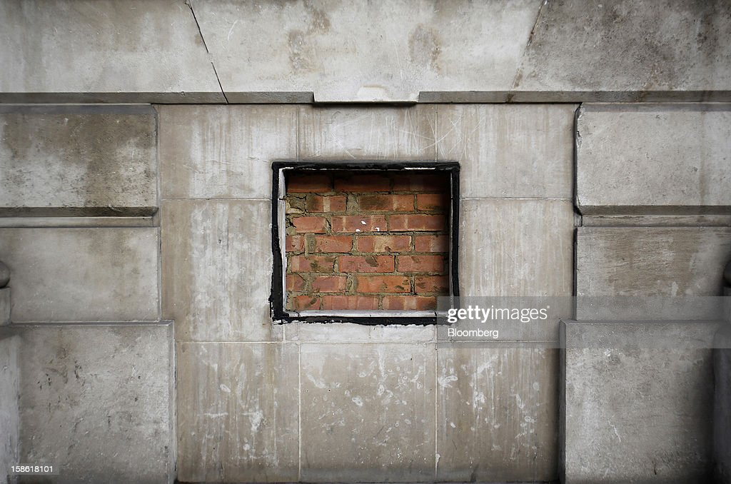 Bricks fill a hole left by an automated teller machine (ATM) removed from a wall outside a Natwest bank branch in London, U.K., on Friday, Dec. 21, 2012. Britain's economy expanded less than previously estimated in the third quarter and the budget deficit unexpectedly widened in November, complicating Prime Minister David Cameron's attempts to bolster the recovery. Photographer: Simon Dawson/Bloomberg via Getty Images