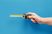 Diy concept.Hand holding tape measure on blue background