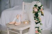 Bridal accessories on a white chair with flowers, perfume shoes. Clothing concept.
