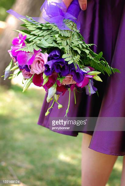 Bridal: Bridesmaid carrying bouquet of colorful flowers at Wedding
