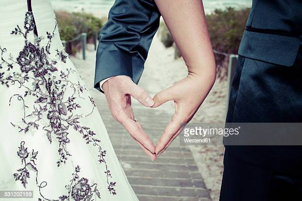 Bridal couple shaping heart with their hands