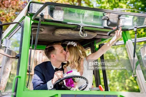 bridal couple sitting in green tractor and kissing after farmer wedding - the groom wears his wedding suit and the blonde haired bride her wedding dress, she holds her bridal bouquet of flowers consisting of white ad pink peonies in her right hand