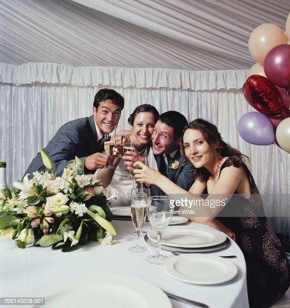 Bridal party toasting champagne in marquee, smiling, portrait